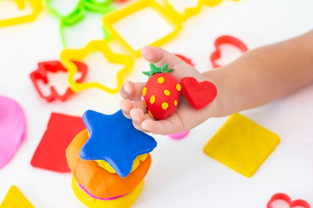 Maluch rzeźbi z kolorowej plasteliny na białym stole. rączka małego dziecka ściska kawałki kolorowej plasteliny. kreatywność dzieci, gry edukacyjne, zdolności motoryczne