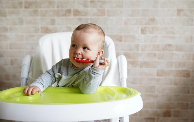 Maluch siedzi na krzesełku do karmienia i gryzie plastikową łyżkę