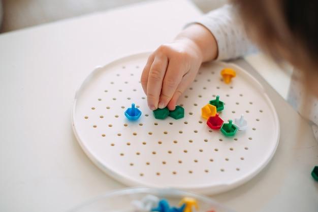 Maluch składa mozaikę z małych części.