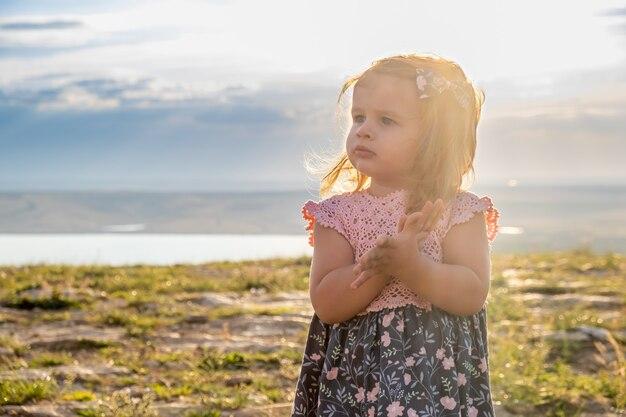Maluch śliczna dziewczyna w pięknej różowej i niebieskiej sukience ociera ręce i odwraca wzrok.