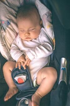 Maluch śpi w foteliku samochodowym. opieka i zdrowie. pierwszy rok życia. mały chłopiec lub dziewczynka jest w samochodzie. zbliżenie.