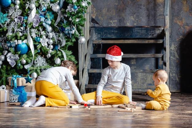 Maluchy chłopcy w czapce mikołaja budują kolej i bawią się zabawkowym pociągiem pod choinką. dzieci z prezentami świątecznymi. czas świąt.