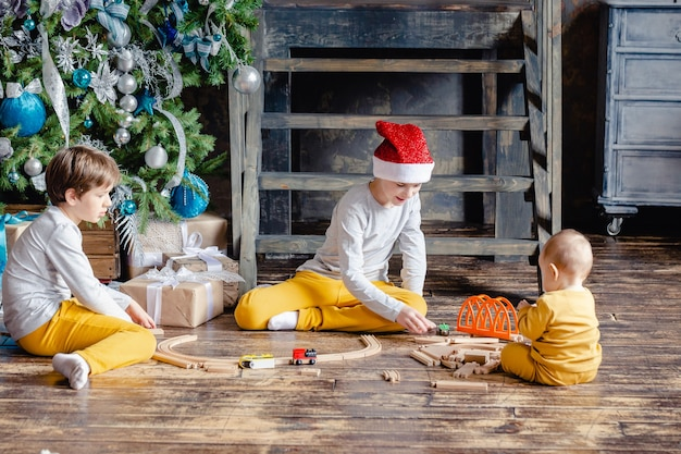 Maluchy chłopcy witj kapelusz świętego mikołaja budujący kolej i bawią się zabawkowym pociągiem pod choinką. dzieci z prezentami świątecznymi. czas świąt.
