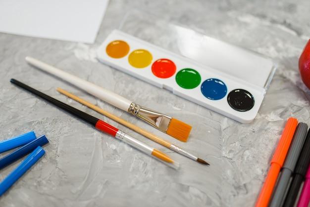 Maluje pędzle i markery na stole w sklepie papierniczym