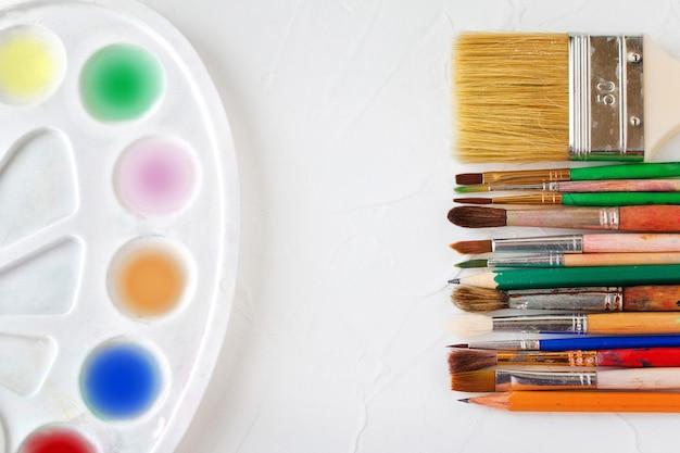 Maluje pędzle o różnych rozmiarach i ołówki do rysowania na białym tle tekstury