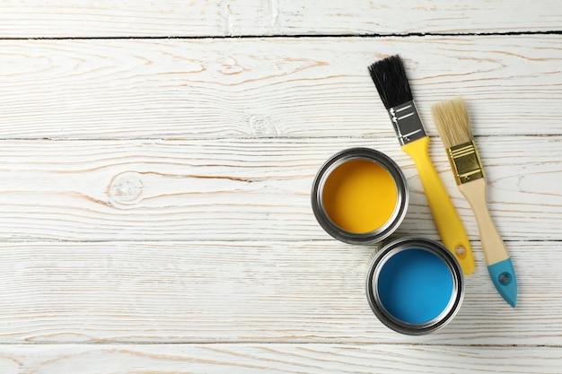 Maluje puszki i muśnięcia na drewnianym stole, widok z góry