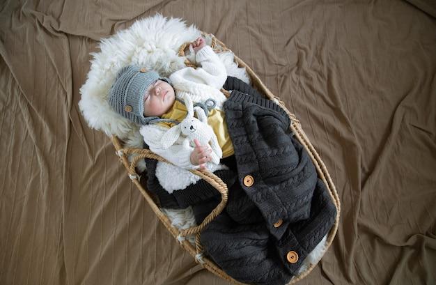 Maluszek śpi słodko w wiklinowej kołysce w ciepłej dzianinowej czapce pod ciepłym kocem z zabawką w rączce.