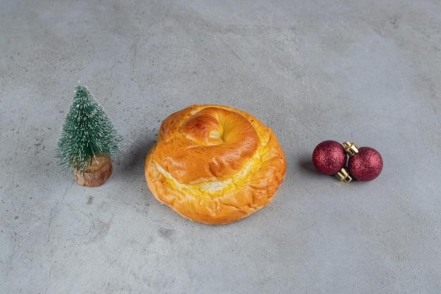 Malutka figurka drzewka, słodka bułka i ozdobne kulki ułożone na marmurowym stole.