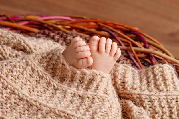 Malutka stopa noworodka. miękkie stopki noworodka na beżowym kocu. dziecięce stopy z zakrzywionymi palcami
