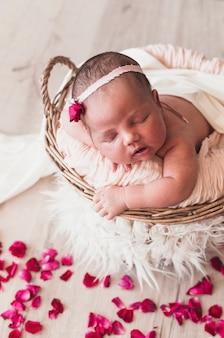 Malutki noworodek w spanie z pałąkiem na głowę