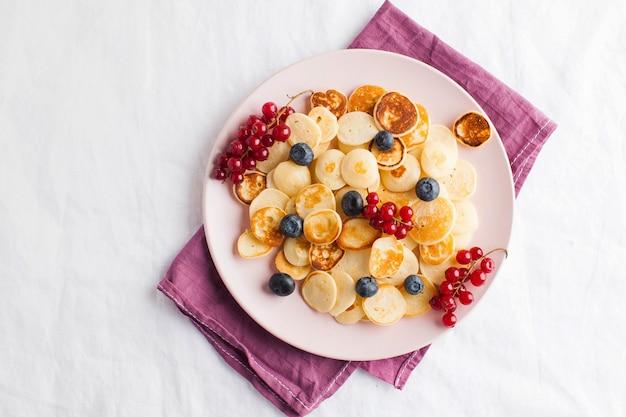 Malutkie naleśniki z jagodami, miodem na białym obrusie. płatki pancake. koncepcja śniadanie, trendy żywieniowe. skopiuj miejsce.