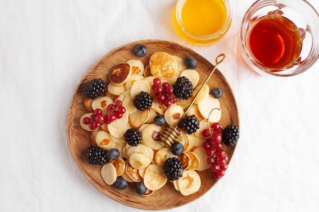 Malutkie naleśniki z jagodami z bliska na białym obrusie. owsianka naleśnikowa. pojęcie trendów śniadaniowych w podaży.