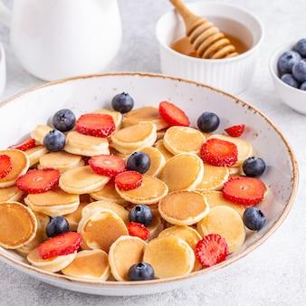 Malutkie naleśniki z truskawkami i jagodami na śniadanie. selektywna ostrość.