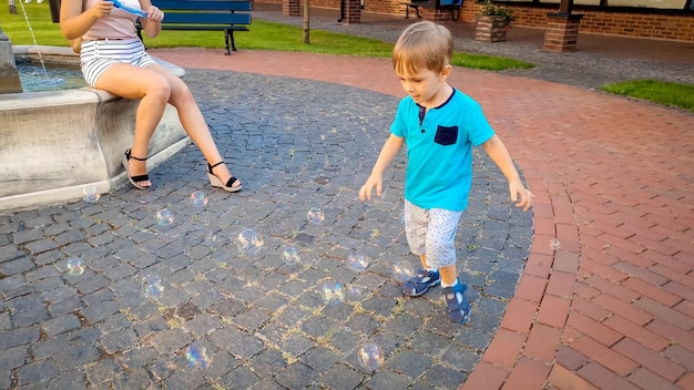 Mały 3-letni chłopiec biegający za kolorowymi bańkami mydlanymi na placu miejskim