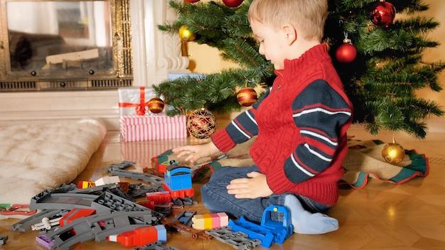 Mały 4-letni chłopiec siedzi na podłodze pod choinką i buduje kolejkę zabawkową