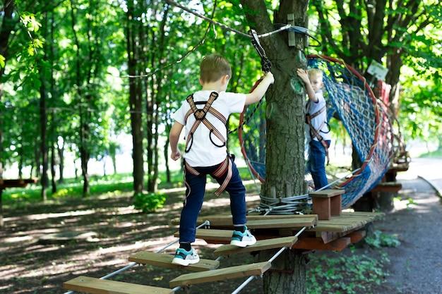 Mały aktywny chłopiec, który wspina się po linie do wesołego miasteczka