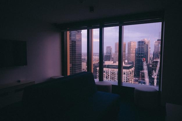 Mały apartament z dużym oknem z widokiem na miejską architekturę