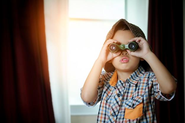 Mały asian chłopca z zabawką żaglówkę w pokoju hotelowym. koncepcja podróży i przygody