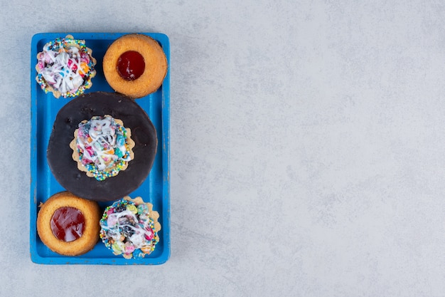 Mały asortyment deserów na niebieskim talerzu na marmurowym stole.