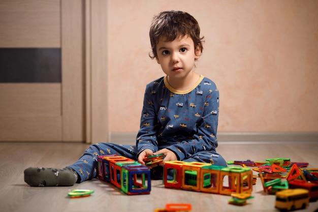 Mały autystyczny chłopiec o europejskim wyglądzie w niebieskiej piżamie gra magnetycznego konstruktora na podłodze w swoim pokoju