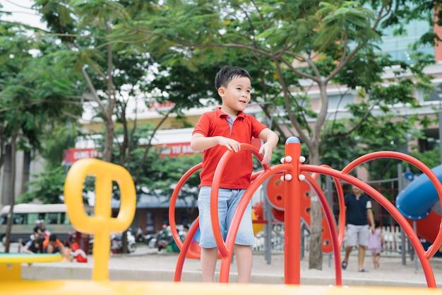 Mały azjatycki chłopiec jeździ na huśtawce i się cieszy