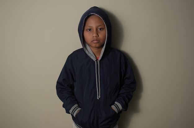 Mały azjatycki chłopiec ubrany w niebieską kurtkę z kapturem na głowie stojący na tle ściany