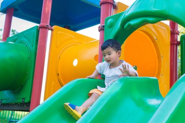 Mały azjatycki dzieciak bawić się obruszenie przy boiskiem