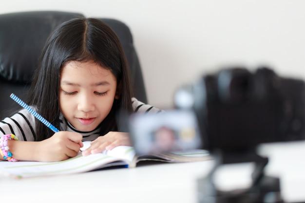 Mały azjatycki dziewczyny obsiadanie przy białym stołem robi streaming na żywo dla społecznościowych