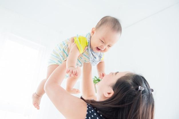 Mały azjatykci dziecko uśmiecha się szczęśliwie podczas gdy bawić się z matką w żywym pokoju