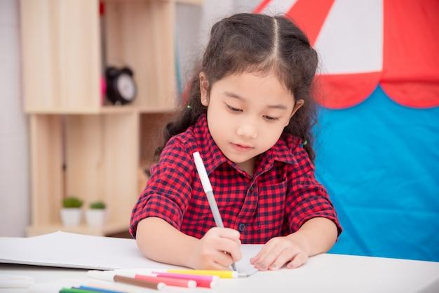 Mały azjatykci dziewczyna rysunku obrazek koloru markierem na stole w domu
