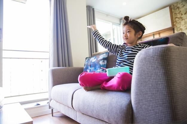 Mały azjatykci dziewczyny łasowanie i oglądać tv na kanapie w żywym pokoju