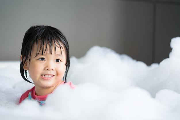 Mały azjatykci dziewczyny obsiadanie w jacuzzi przy łazienką z pianą.