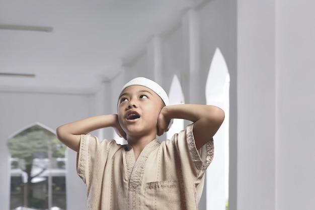 Mały azjatykci muzułmański dzieciaka modlenie