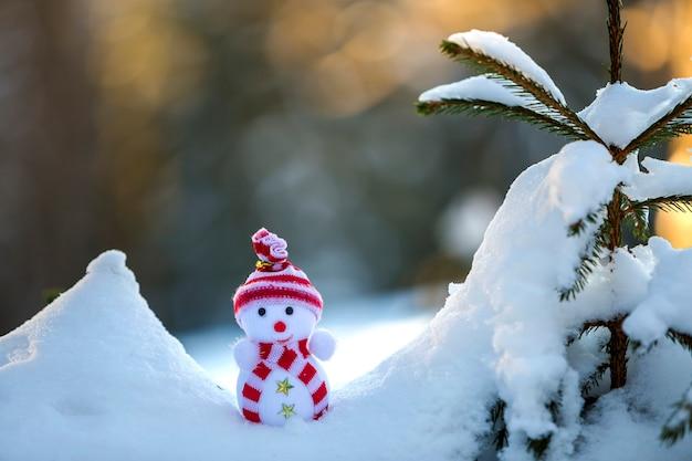 Mały bałwanek zabawka w czapce i szaliku w głębokim śniegu na zewnątrz