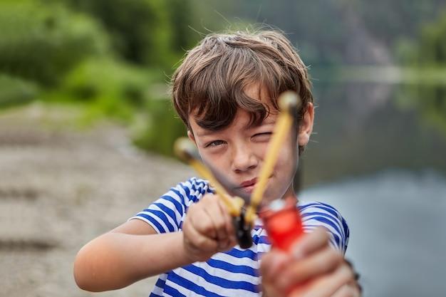 Mały biały chłopiec stoi w lesie z procą w rękach i szykuje się do strzelania, rozsypując się