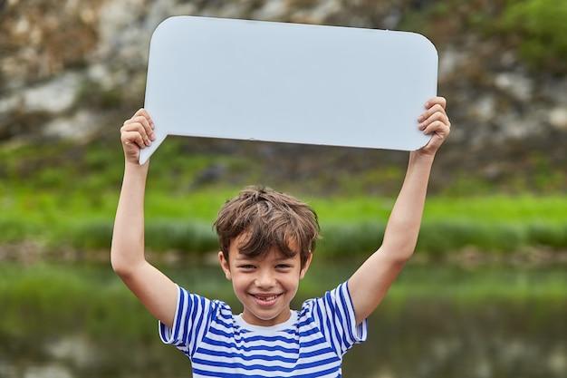 Mały biały chłopiec trzyma pusty strom papieru i uśmiecha się, jest w lesie, a za nim rzeka, ekoturystyka.