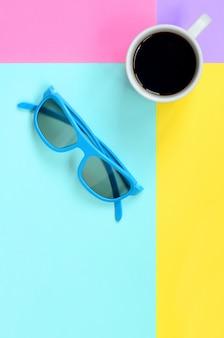 Mały biały kubek kawy i niebieskie okulary onfashion pastelowy niebieski, żółty, fioletowy i różowy papier