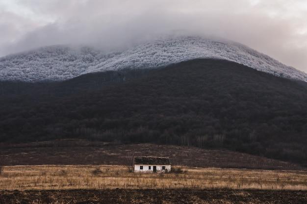 Mały biały pojedynczy dom w polu z mgłą na górze