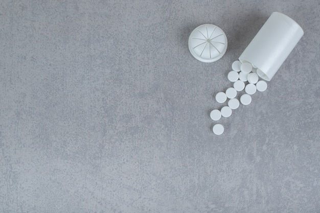 Mały biały słoik białych tabletek na szarej powierzchni