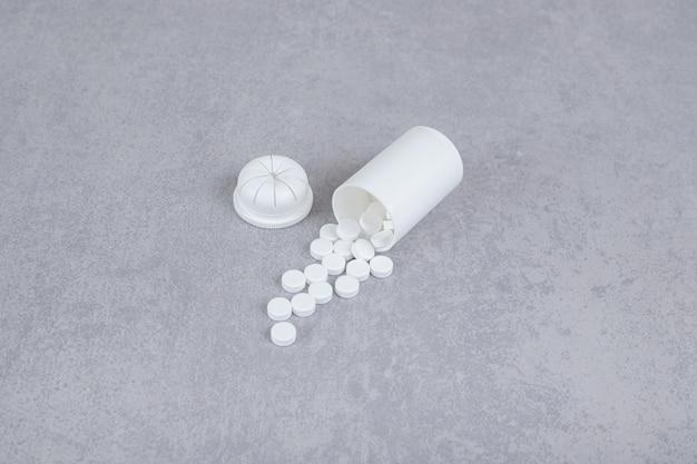 Mały biały słoik białych tabletek na szarym tle.