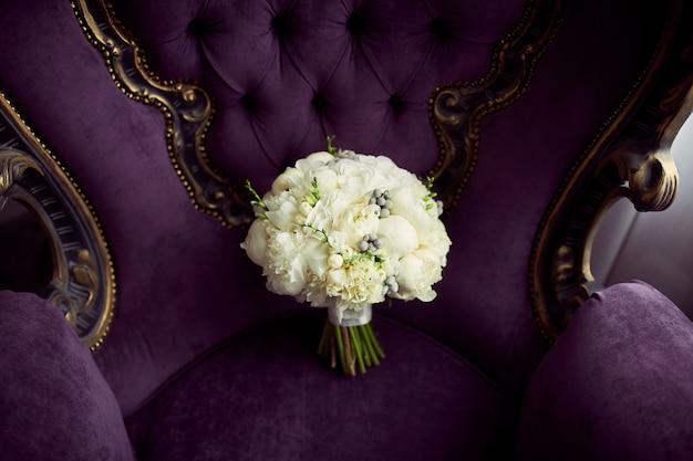 Mały biały ślubny bukiet stoi na fiołkowym krześle