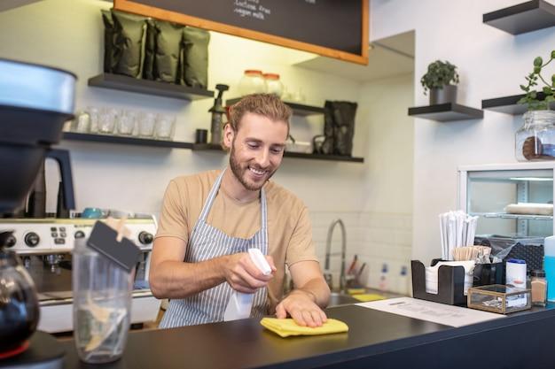 Mały biznes. brodaty, radosny młody mężczyzna wycierający blat w swojej kawiarni