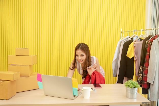 Mały biznes koncepcja. młody sprzedawca pracuje online w domu z technologii sieci bezprzewodowej.