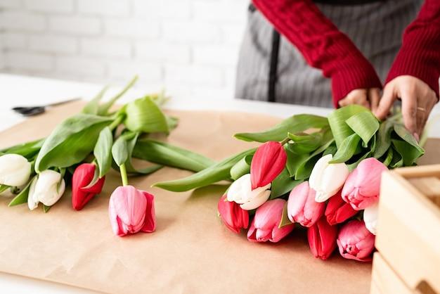 Mały biznes. kwiaciarnia kobieta robi bukiet świeżych kolorowych tulipanów