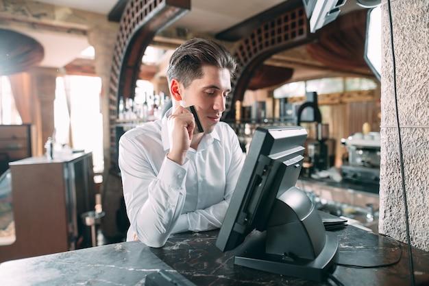 Mały biznes, ludzie i obsługa - szczęśliwy człowiek lub kelner w fartuchu przy kasie z kasą pracującą w barze lub kawiarni.