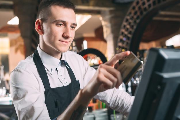 Mały biznes, ludzie i usługowy pojęcie, - szczęśliwy mężczyzna lub kelner w fartuchu przy kontuarem z cashbox pracuje przy barem lub sklep z kawą
