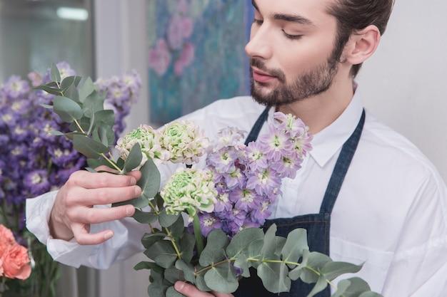 Mały biznes. mężczyzna kwiaciarnia w kwiaciarni. wykonywanie dekoracji i aranżacji