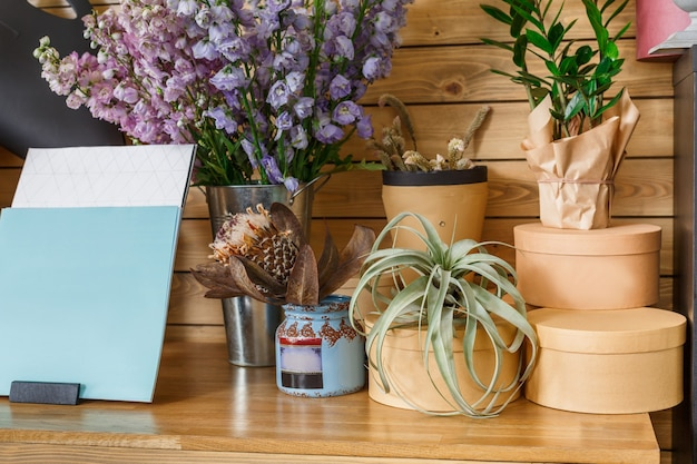 Mały biznes. nowoczesne wnętrze kwiaciarni. studio florystyczne, dekoracje i aranżacje. dostawa kwiatów i sprzedaż roślin domowych w doniczkach, drewniana gablota z obecnymi pudełkami zbliżenie.
