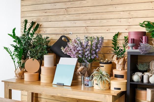 Mały biznes. nowoczesne wnętrze kwiaciarni. studio florystyczne, sprzedaż dekoracji i aranżacji. dostawa kwiatów oraz sprzedaż roślin domowych w doniczkach, gablota drewniana.