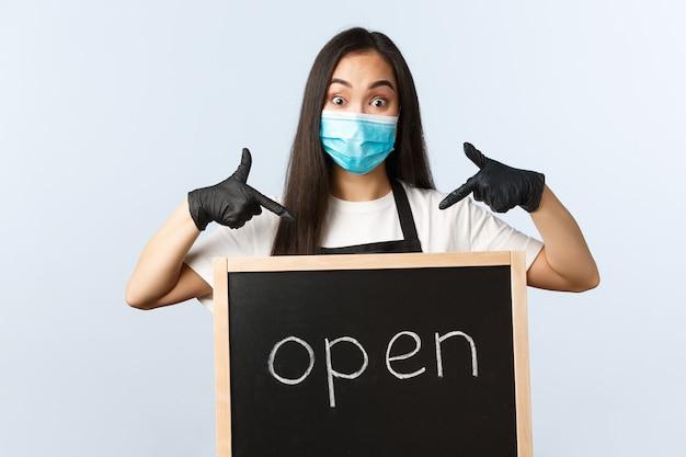 Mały biznes, pandemia covid-19, zapobieganie koncepcji wirusów i pracowników. podekscytowany ładny azjatycka kobieta barista, kawiarnia lub pracownik sklepu w masce medycznej, wskazując na jesteśmy otwartym znakiem.